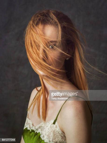 Studio portrait of young woman with wind blown red hair