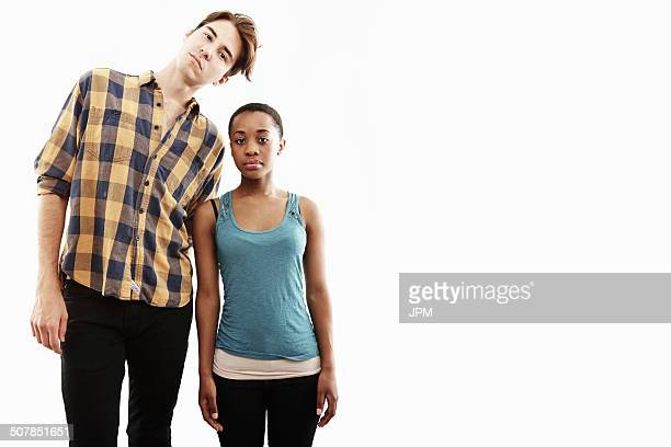 studio portrait showing contrasting height of young couple - tall high stock pictures, royalty-free photos & images