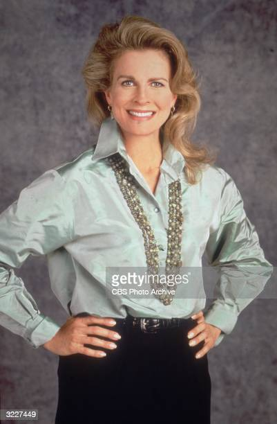 Studio publicity portrait of American actor Candice Bergen wearing a satin blouse and a long necklace with her hands on her hips dressed in character...