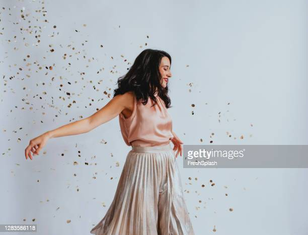 studio shopt of a beautiful smiling elegant woman dancing showered with confetti - pink skirt stock pictures, royalty-free photos & images