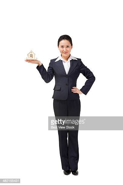 studio shot business woman holding  a toy house