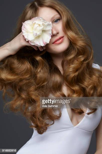 studio shot of a beautiful brunette with long wavy hair holding a peony