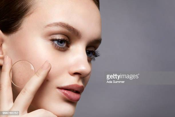 studio shot of a beautiful young woman holding a magnifying glass to her skin - faltenreduktion stock-fotos und bilder