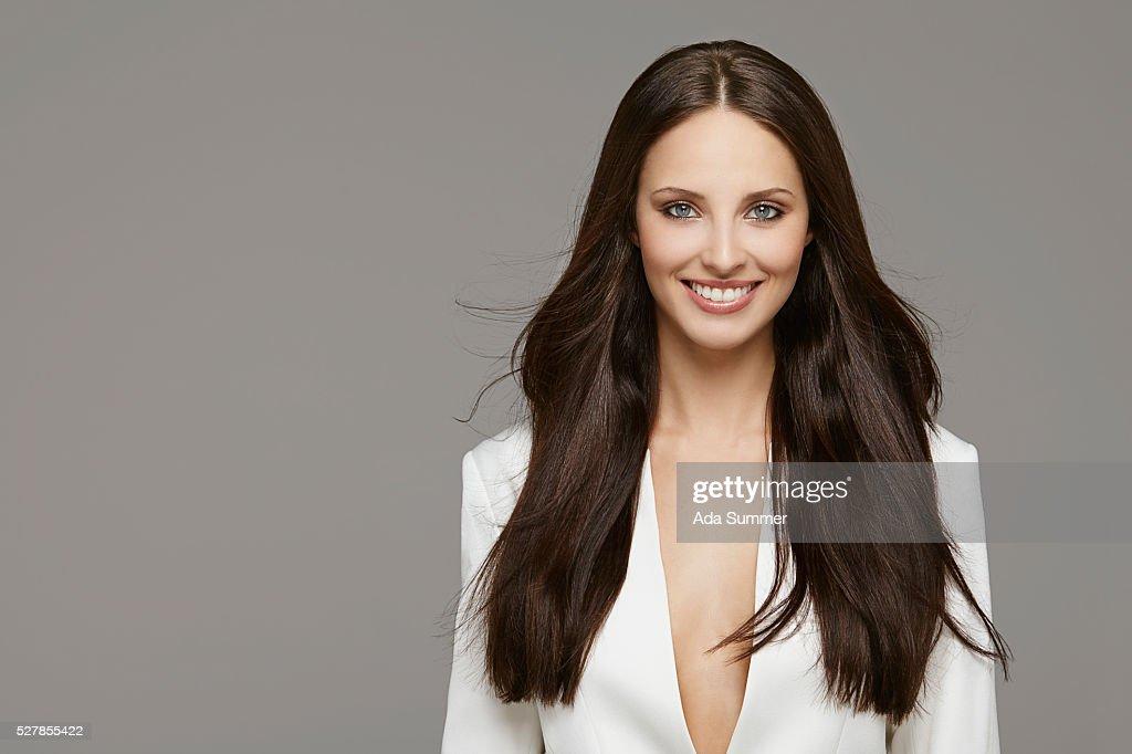studio shot of a brunette in a white blazer : Foto de stock