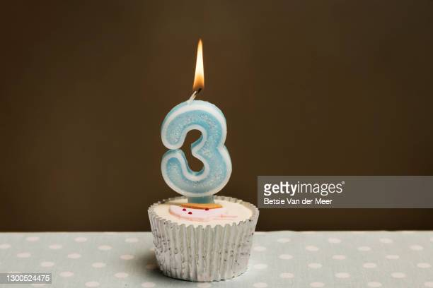 studio shot of a cupcake with a number 3 candle with a burning flame on top. - birthday candle stock pictures, royalty-free photos & images