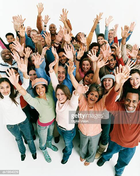 Studio Shot of a Large Mixed Age, Multiethnic Group of Men and Women Cheering With Their Arms in the Air