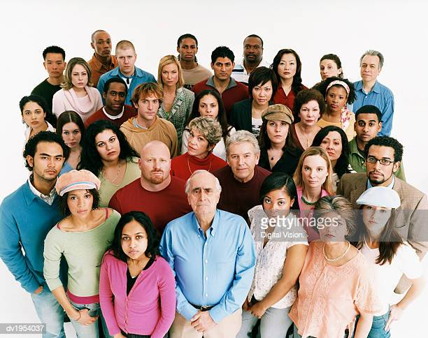 studio shot of a large mixed age, multiethnic group of men and women staring at the camera in a displeased way - mixed age range stock pictures, royalty-free photos & images