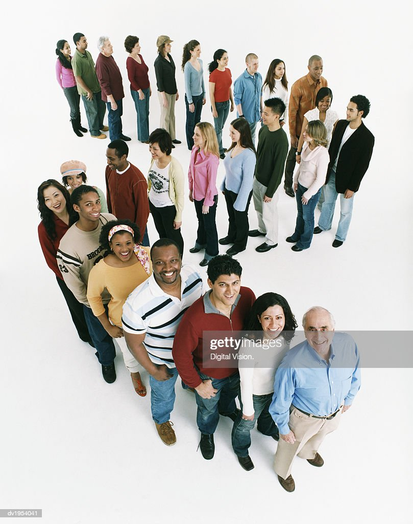 Studio Shot of a Large Mixed Age, Multiethnic Group of Men and Women Waiting in Line, Looking up at the Camera and Smiling : Stock Photo