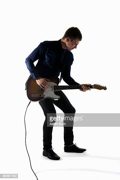 Studio shot of a man playing an electric guitar