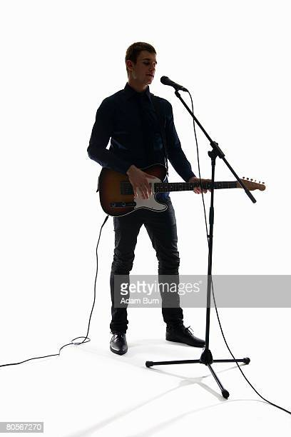 studio shot of a man singing into a microphone and playing an electric guitar - マイクスタンド ストックフォトと画像