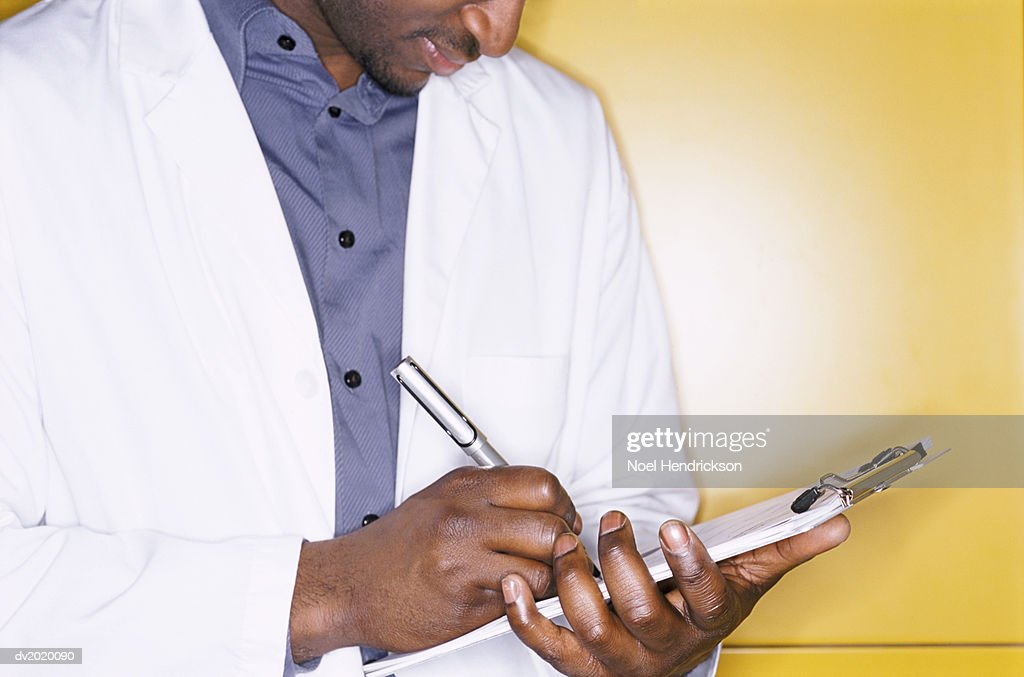 Studio Shot of a Man Wearing a White Lab Coat Writing on a Clipboard : Stock Photo