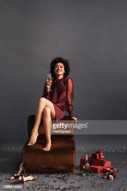 studio shot of a smiling african american woman sitting barefoot and having a glass of champagne with a pile of christmas presents on the floor - maroon stock pictures, royalty-free photos & images