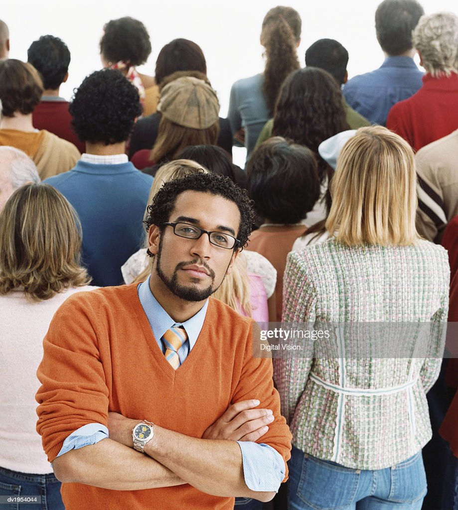 Studio Shot of a Well Dressed Man Standing in Front of a Crowd of People With Their Backs Turned : Stock Photo