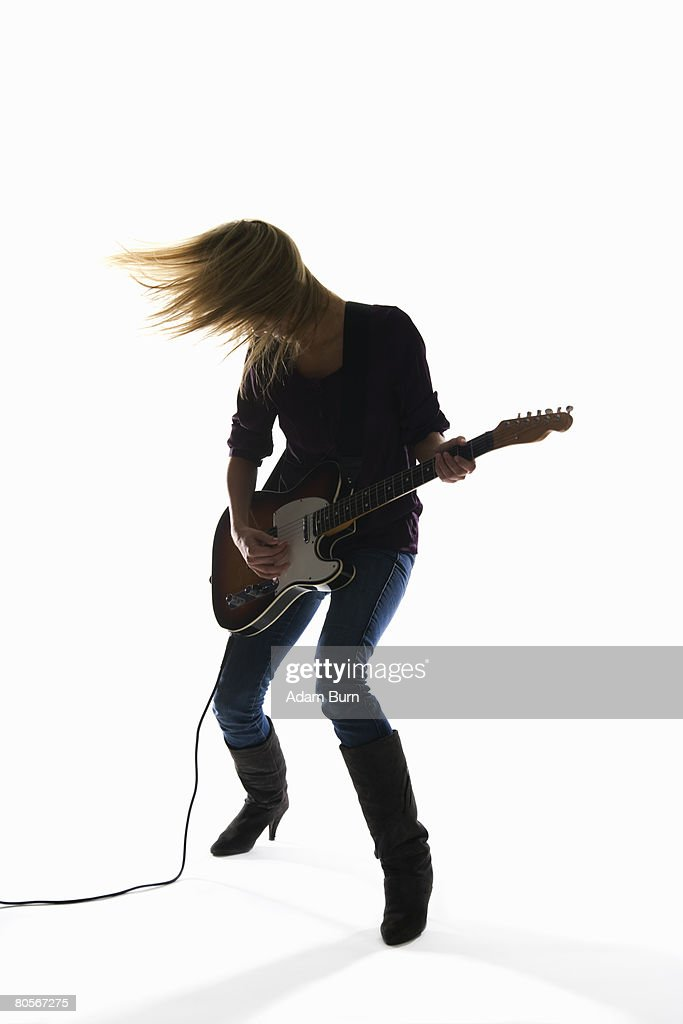 Studio shot of a woman playing an electric guitar : Stock Photo
