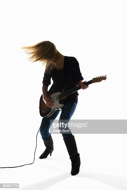 studio shot of a woman playing an electric guitar - rock object fotografías e imágenes de stock