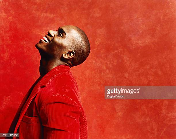 studio shot of a young man in a casual red jacket, laughing and looking upwards - coat stockfoto's en -beelden