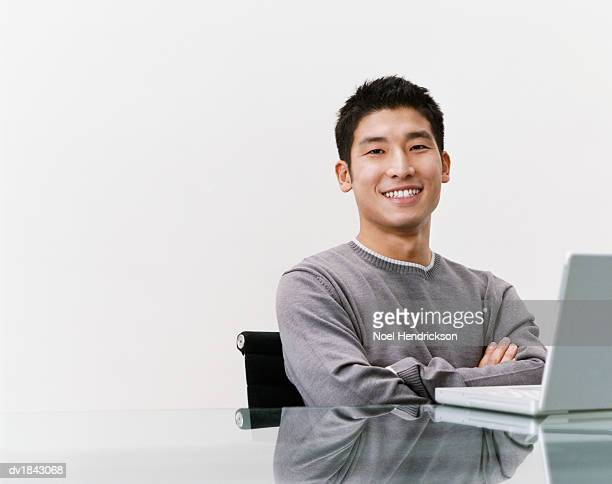 Studio Shot of a Young Man Sitting at a Table with a Laptop Computer