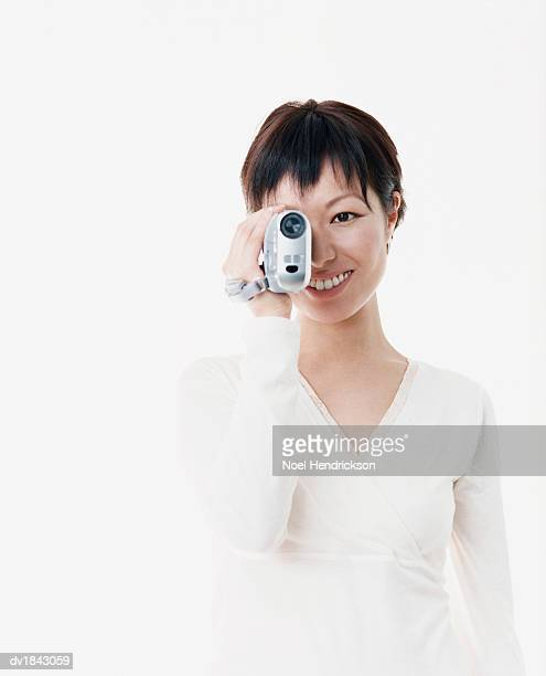 Studio Shot of a Young Woman Filming with a Camcorder