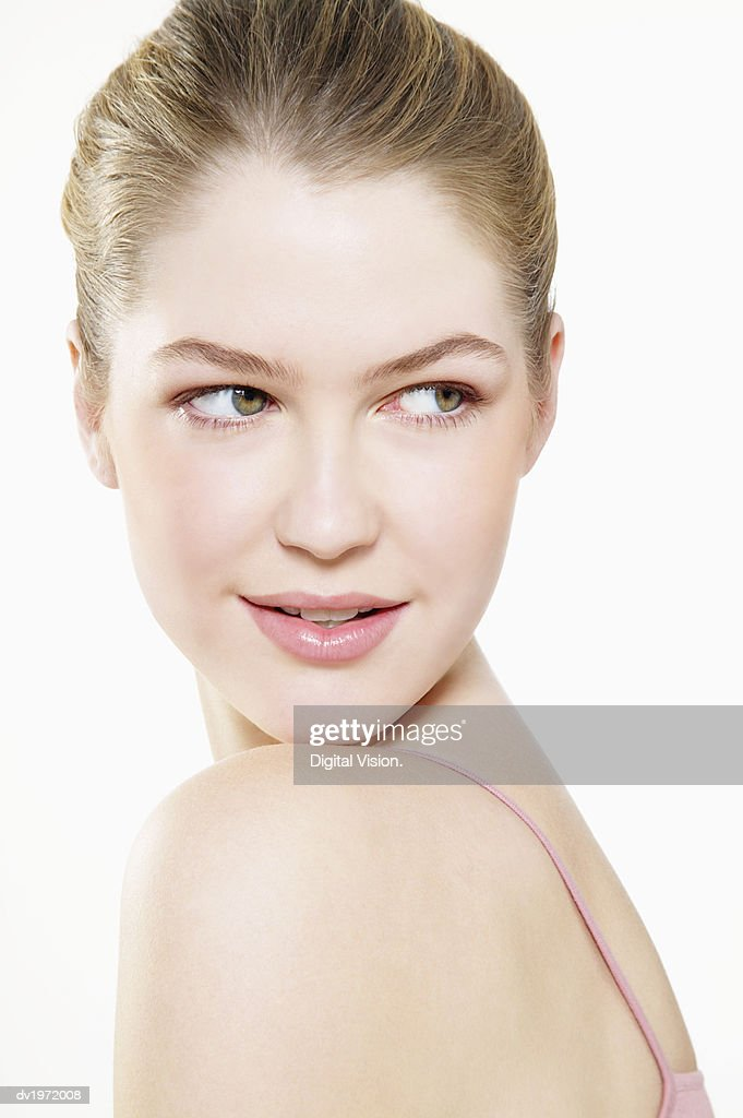 Studio Shot of a Young Woman Looking Back Over Her Shoulder : Stock Photo