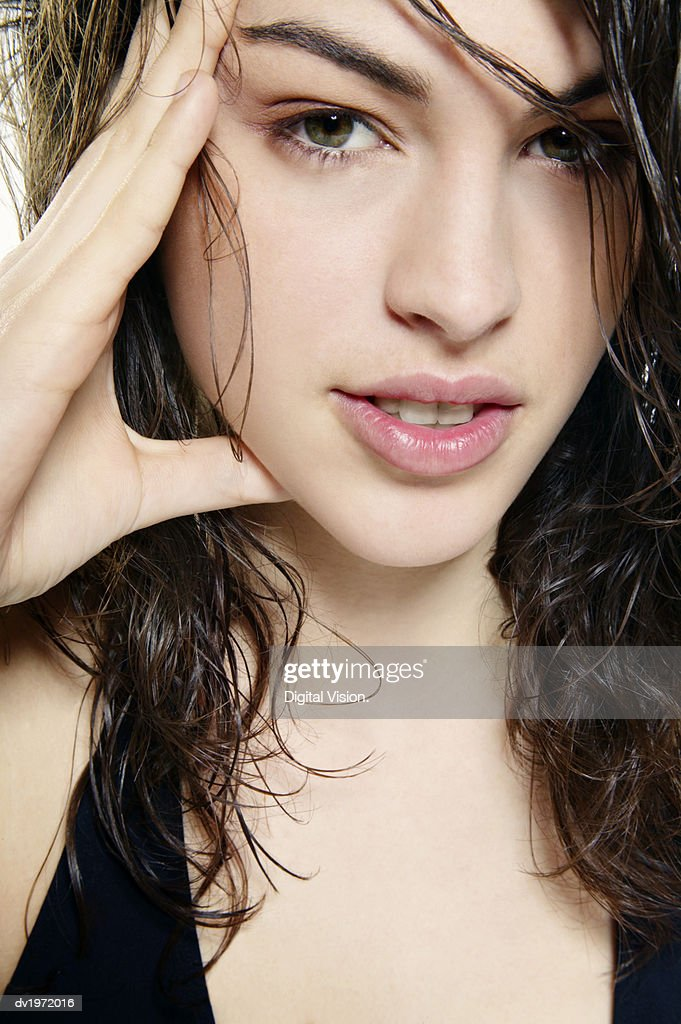 Studio Shot of a Young Woman with Wet and Tousled Hair Holding Her Hand to Her Head : Stock Photo