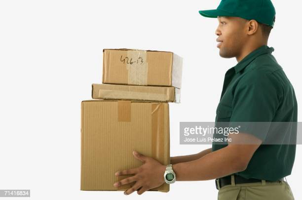 Studio shot of African delivery man carrying boxes