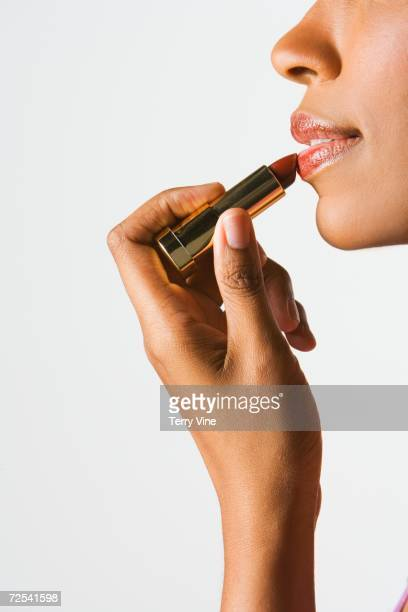 Studio shot of African woman applying lipstick