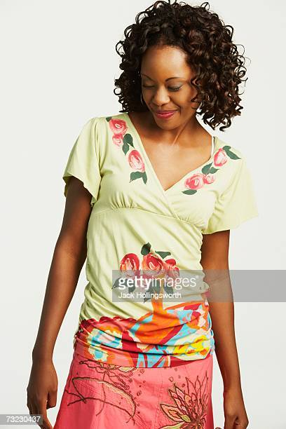 studio shot of african woman smiling and looking down - down blouse stock pictures, royalty-free photos & images