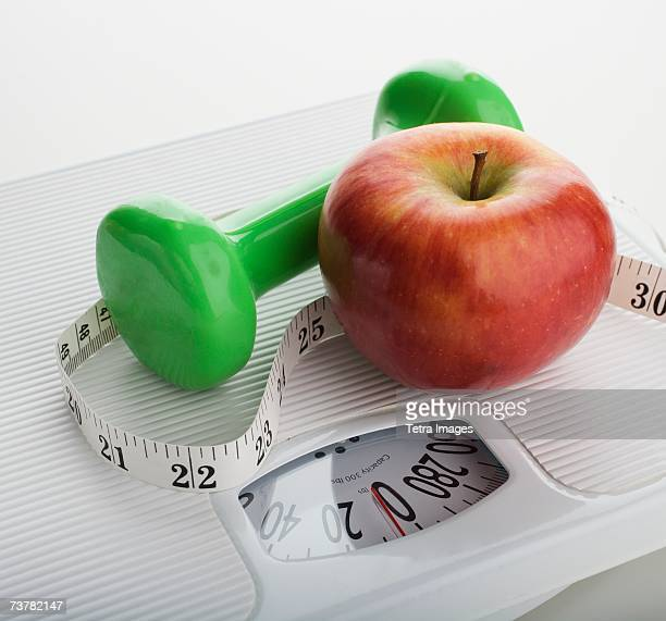 Studio shot of apple, scale, tape measure and dumbbell