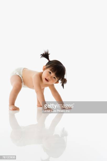 studio shot of asian baby crawling - diaper girl photos et images de collection