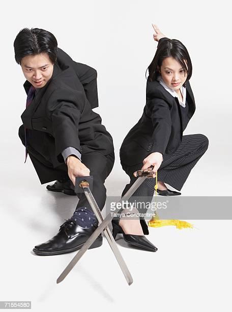 Studio shot of Asian businesspeople with crossed swords
