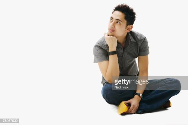 Studio shot of Asian man sitting cross-legged
