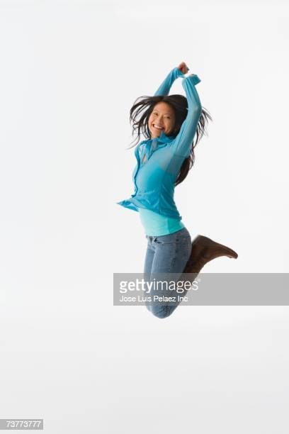 Studio shot of Asian woman jumping