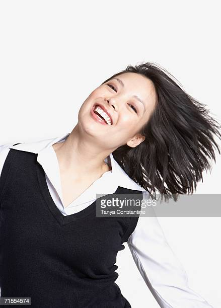 Studio shot of Asian woman tossing hair and smiling