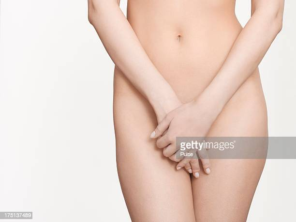 studio shot of attractive naked young woman covering her crotch. - pube foto e immagini stock