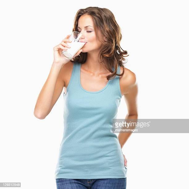 Studio shot of attractive young woman drinking milk