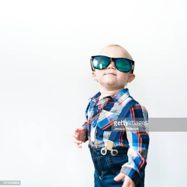 Studio shot of baby boy (12-17 months) wearing sunglasses