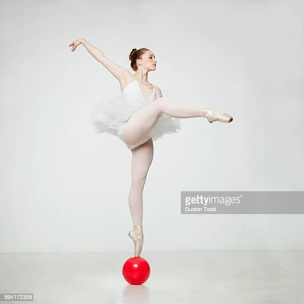 Studio shot of ballet dancer balancing on ball