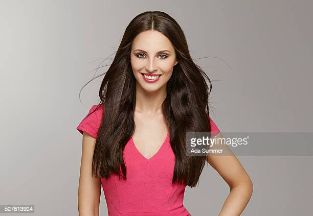 studio shot of beautiful brunette woman wearing pink dress - straight hair stock pictures, royalty-free photos & images