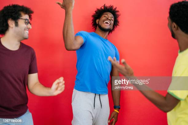 studio shot of black and mixed race male friends dancing - royal blue stock pictures, royalty-free photos & images
