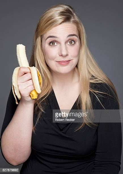 studio shot of blond haired woman holding banana - fat blonde women stock photos and pictures