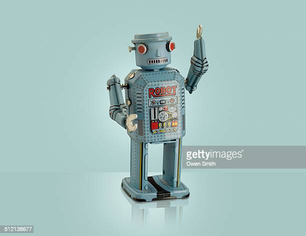Studio shot of blue robot with arm raised
