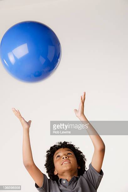 Studio shot of boy (8-9) tossing blue ball