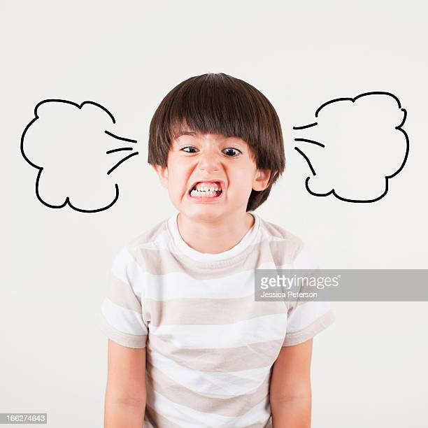 Studio shot of boy (6-7) with smoke puffs coming out of ears