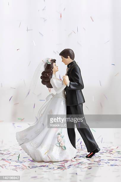 Studio shot of bride and groom figurines dancing