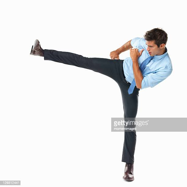 Studio shot of business man delivering high side kick