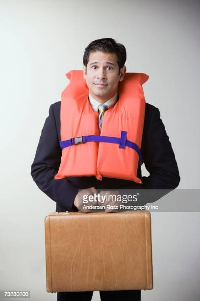 Studio shot of businessman wearing life jacket and holding briefcase