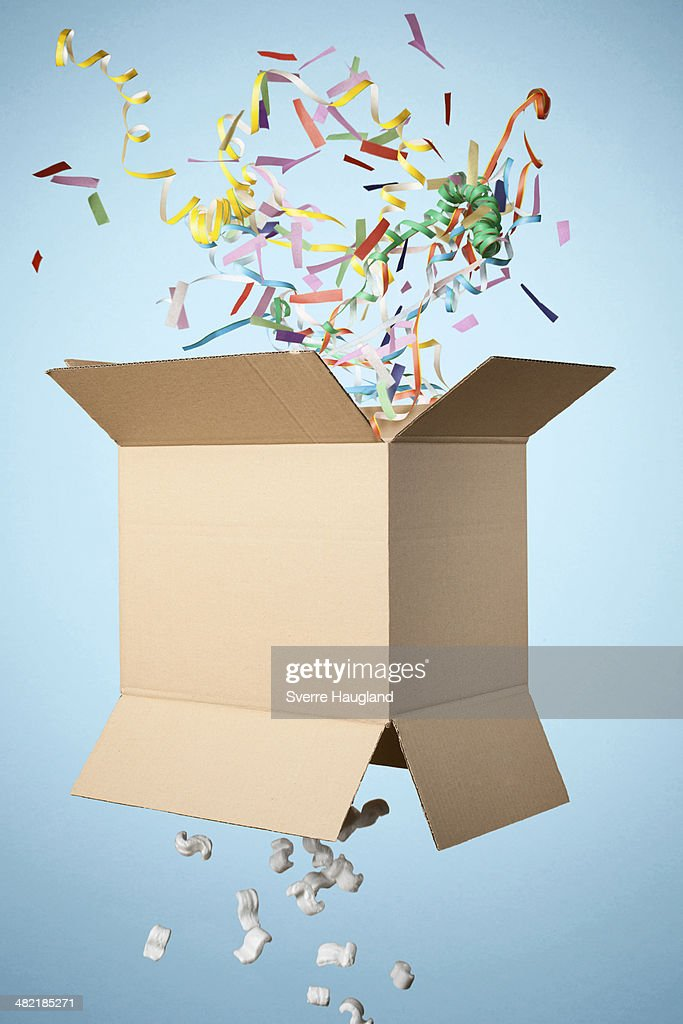 Studio shot of cardboard box with streamers exploding out : Stock Photo