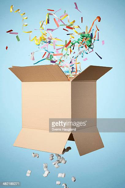 studio shot of cardboard box with streamers exploding out - cardboard box stock pictures, royalty-free photos & images