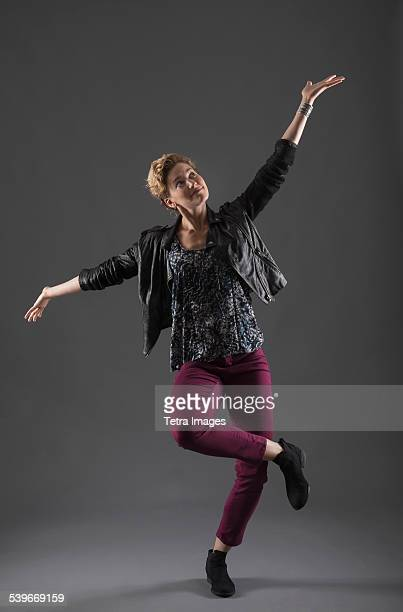 Studio shot of cheerful woman with arms raised