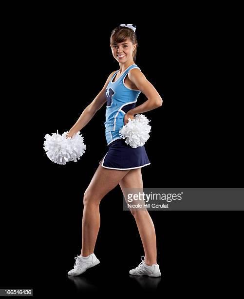 studio shot of cheerleader (16-17) striking pose - ado minijupe photos et images de collection